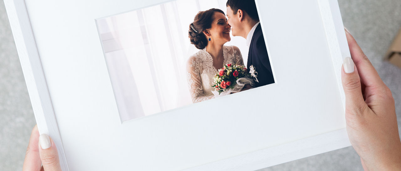 Holding a framed wedding picture